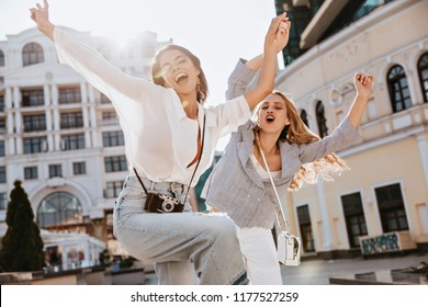 Excited woman in white blouse funny dancing on the street. Laughing stylish girls fooling around during city photoshoot.