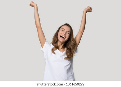 Excited woman in white t-shirt raised hands celebrating success achievement pose studio shot. Female feels euphoric motivated by unbelievable news received new opportunity passed exam got job of dream