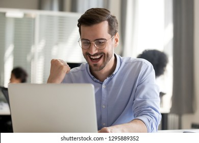 Excited worker sitting at desk in coworking space use computer reading message looking at device screen received great unbelievable opportunity or reward. Motivated employee celebrating job promotion