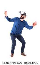 Excited young adult man bending and crouching having virtual reality glasses experience. Full body isolated on white background.