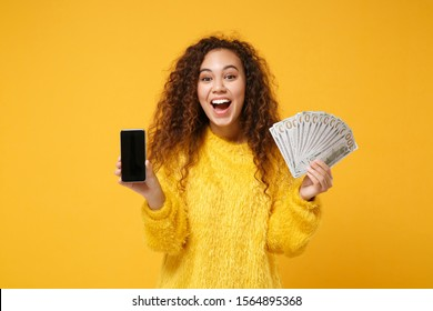 Excited young african american girl posing isolated on yellow background. People lifestyle concept. Mock up copy space. Hold mobile phone with blank empty screen fan of cash money in dollar banknotes
