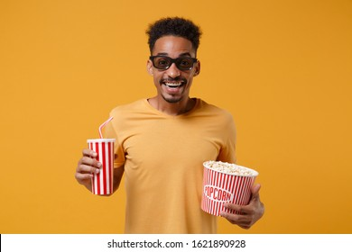 Excited young african american guy in 3d imax glasses posing isolated on yellow orange background. People lifestyle concept. Mock up copy space. Watching movie film hold bucket of popcorn cup of soda