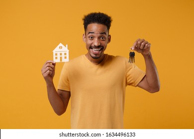 Excited young african american guy in casual t-shirt posing isolated on yellow orange background, studio portrait. People lifestyle concept. Mock up copy space. Hold in hands house and bunch of keys