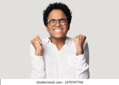 Excited young african american lucky woman in glasses feeling joyful, celebrating success, important achievement, isolated on gray studio background. Smiling euphoric black girl showing yes gesture.