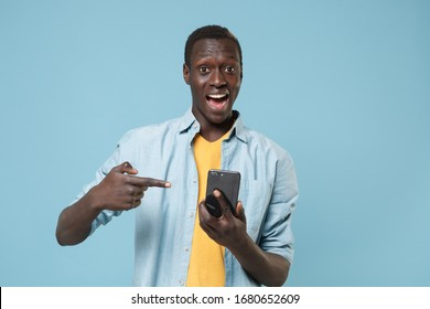 Excited young african american man guy in casual shirt, yellow t-shirt posing isolated on blue wall background. People lifestyle concept. Mock up copy space. Pointing index finger on mobile phone