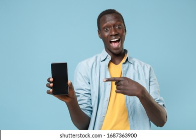 Excited young african american man guy in casual shirt, yellow t-shirt posing isolated on blue wall background. People lifestyle concept. Pointing index finger on mobile phone with blank empty screen - Shutterstock ID 1687363900