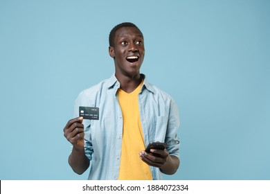 Excited young african american man 20s in casual shirt, yellow t-shirt isolated on blue background. People lifestyle concept. Mock up copy space. Using mobile phone hold credit bank card looking up