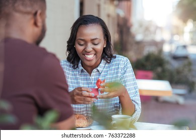 Excited young African woman opening a wrapped present from her boyfriend while sitting together at a sidewalk cafe