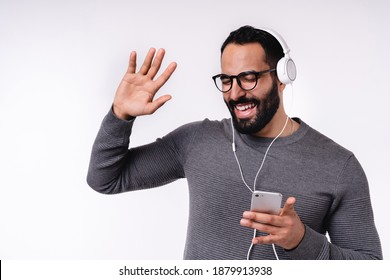 Excited young Arab man listening to the music and dancing in headphones isolated over white background
