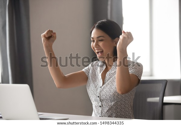 Excited young asian business woman celebrating successful financial project results, attracting important corporate client, dream goal achievement. Euphoric employee got increased salary or promotion.