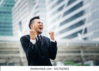 Excited young asian businessman happy and hurrah while standing outdoors with office building in the background