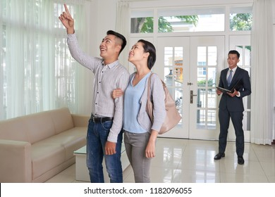 Excited young Asian couple visiting house for sale