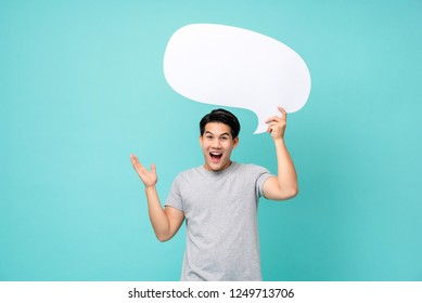 Excited young Asian man with empty speech bubble studio shot isolated on light blue background