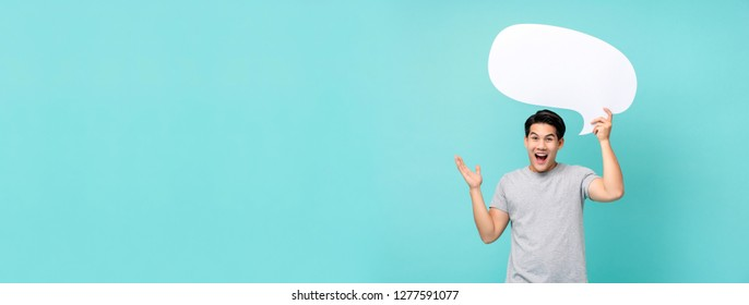 Excited young Asian man holding speech bubble with empty space for text studio shot isolated on light blue banner background