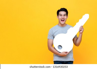 Excited young Asian man holding big mockup car key studio shot in yellow backround with copy space