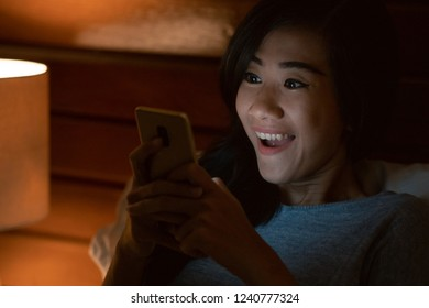 excited young asian woman in bed using cell phone. happy social media user