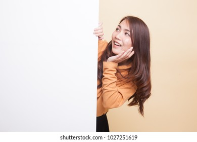 Excited young Asian woman with blank sign on beige background