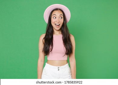 Excited young asian woman girl in casual pink clothes hat posing isolated on green wall background studio portrait. People lifestyle concept. Mock up copy space. Keeping mouth open, looking aside
