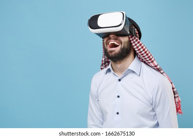 Excited young bearded arabian muslim man in keffiyeh kafiya ring igal agal casual clothes isolated on pastel blue background. People religious lifestyle concept. Mock up copy space. Watch in headset