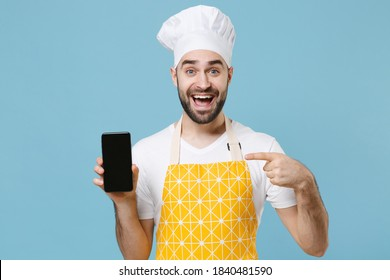 Excited young bearded male chef or cook baker man in apron white t-shirt toque chefs hat isolated on blue background. Cooking food concept. Point index finger on mobile phone with blank empty screen