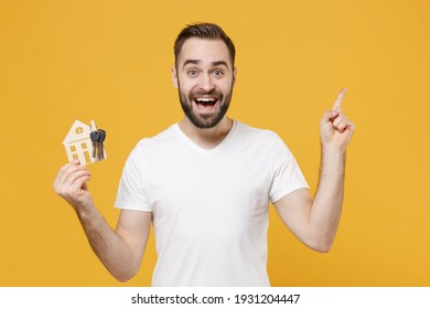 Excited young bearded man guy in white casual t-shirt isolated on yellow background studio portrait. People lifestyle concept. Mock up copy space. Hold house bunch of keys, pointing index finger up