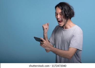 Excited young bearded man playing mobile games in blue background. Asian young hipster playing mobile game and win, half body shot. Young generation hipster relaxing concept.