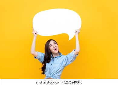 Excited young beautiful Asian woman holding and looking up to speech bubble with empty space for text on colorful yellow background