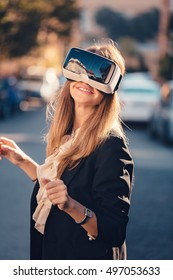 Excited young beautiful girl gesture testing virtual reality 3D video glasses VR headset dressed in a office outfit impressed by augmented reality on the street and beautiful autumn sun light colors
