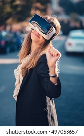 Excited young beautiful girl wearing virtual reality 3D video glasses VR headset dressed in a office outfit impressed by augmented reality on the street and beautiful autumn sun light colors