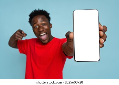 Excited Young Black Man Pointing On Smartphone With Blank White Screen In His Hands, Emotional African American Guy Demonstrating Copy Space For Your Design, Standing On Blue Background, Mockup