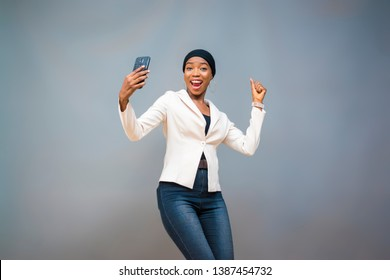 excited young black muslim lady holding her phone