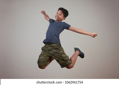 Excited young boy jumps against a wall background