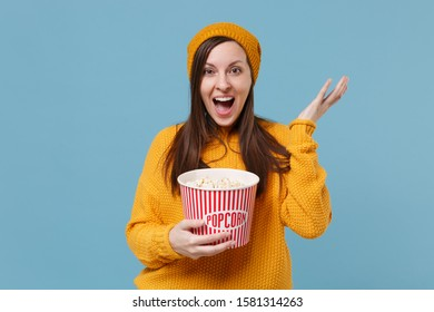 Excited young brunette woman girl in sweater and hat posing isolated on blue background. People emotions in cinema lifestyle concept. Mock up copy space. Watching movie film holding bucket of popcorn