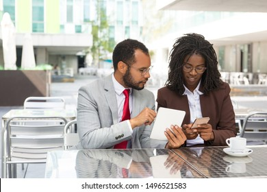 Excited young business colleagues using gadgets in street cafe. Business man and woman sitting in coffee shop, showing tablet and smartphone screens to each other. Wireless technology concept