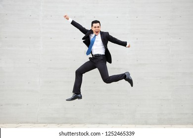excited Young businessman running and jumping