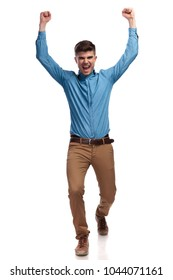 excited young casual man celebrating success with fists in the air on white background