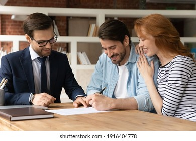 Excited young Caucasian couple sign contract make deal buy house at male relator or broker. Happy man and woman spouses clients put signature close agreement with agent. Rental, realty concept.