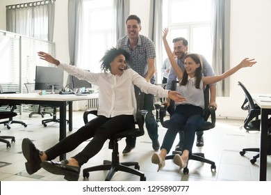 Excited young cheerful multiracial diverse colleagues having fun riding on office chairs in coworking space. Active happy millennial workers take a break enjoy play game laughing together at workplace