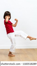excited young child showing her strength with fists raised, enjoying exercising martial art, tai chi, kung fu or taekwondo for fun kid sport and energy over wooden floor, white background