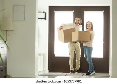 Excited young couple carrying boxes moving into new home concept, happy married family holding belongings arriving entering big own bought or rented house, buying real estate, mortgage and relocation