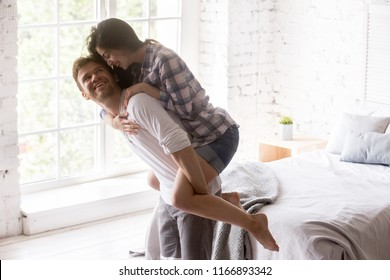 Excited young couple having fun at home, happy girl piggyback her boyfriend in white bedroom, strong millennial man carrying lover on his back, spouses playing funny game laughing together