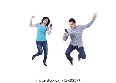 Excited young couple jumping with mobile phone