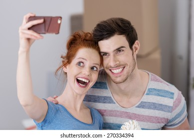 Excited young couple in a new home posing for a selfie on their mobile phone with big cheesy playful grins