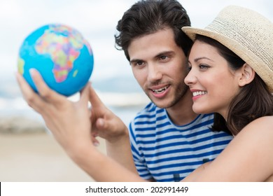 Excited young couple planning their holiday holding up a globe and pointing to a travel destination with focus to the attractive woman in a trendy straw hat