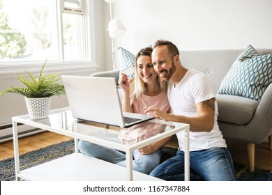 Excited young couple shopping online, holding credit card and looking at laptop at home