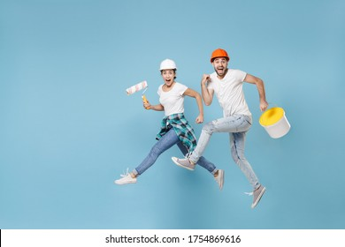 Excited young couple woman man in protective helmet hardhat jumping with paint bucket, paint roller isolated on blue background. Instruments accessories renovation apartment room. Repair home concept