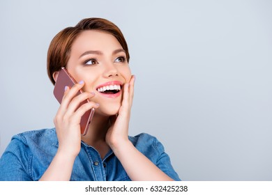 Excited young cute girl is talking on her smartphone and smiling. She is wearing jeans shirt and behind her is a pure blue background
