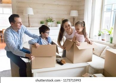 Excited young family have fun together while unpacking moving in, playful cute kids hide in boxes when opening packages with belongings, happy parents play game with children relocating to new house