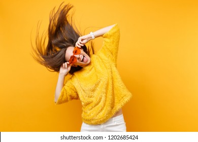 Excited young girl in fur sweater holding heart orange glasses fooling around in studio jumping with fluttering hair isolated on yellow background. People sincere emotions lifestyle. Advertising area