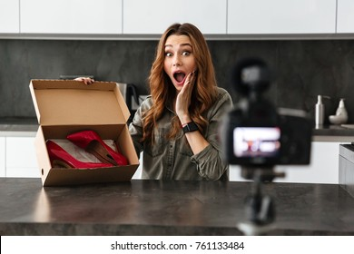 Excited young girl recording her video blog episode about new high stiletto shoes while sitting at the kitchen table at home